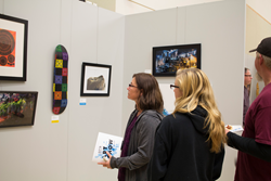 Art admirers take in works during the 2016 President's Art Show at Salt Lake Community College.