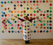 Artist, Anne Labovitz, wearing apron filled with artist tiles in front of participant's engagement pieces