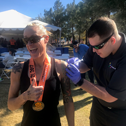 Runner receives IM Shot from ReSquared Medical after competing at Pumpkinman Triathlon.