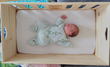 BabyCrate viewed from above with sleeping newborn baby inside