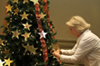 "Members of the community place stars purchased in memory or honor of loved ones on HOW's ""Tree of Life"" during the annual reception."