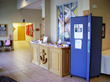 A three panel tackable display tower displays information next to a church welcome desk