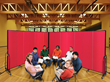 Students gathered in a circle each reading a book with a red portable partition behind them