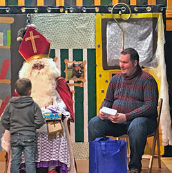 St. Nicholas, with assistance from Joshua Barrett, Chievres Branch Manager, presents a gift to a young boy.