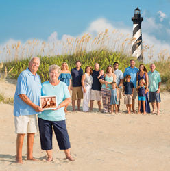 Extended family poses in front of the Cape Hatteras Lighthouse with grandparents holding a photo of their first Hatteras Island vacation in the 1970's