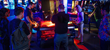 Players face off across an air hockey table in the games room at MAGFest 2018.