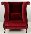 Christopher Guy designed contemporary upholstered red velvet wing chair with ebonized trim