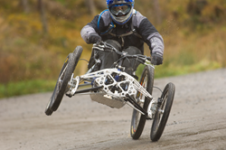 Adaptive four-wheel downhill mountain bike on a trail.