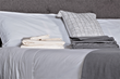 Grund bed with white grey sheets and grey throw
