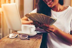 a woman holding money bills