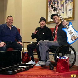 Eric Howk Receives a Goldfinch Guitar as a Thank You Gift from NTI during the interview with Mike Sanders, Director of NTI and bassist Zach Carothers.