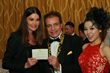 Actress Janice Dickinson is presented with a W1 Coin Certificate from Steven Nia, Chairman and CEO of Wardour Studios and Angelina Leo, COO of Wardour Studios