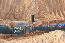 A pipe in the ground prior to being buried.