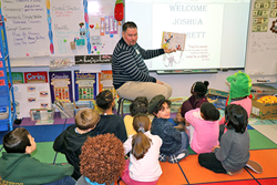 Joshua Barret reads to students at SHAPE American Elementary School for Read Across America Day.