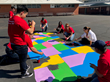 Teacher Created Materials staff paints the US map on the blacktop at Carl E. Gilbert Elementary School
