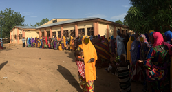 Caretakers in Zambia waiting to get their infants immunized and receive case transfers.