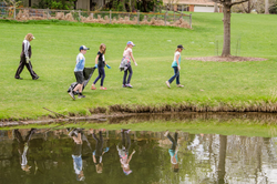 children walking through park reflected in pond