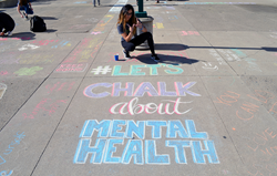 Student writes on campus sidewalk: let's chalk about mental health.