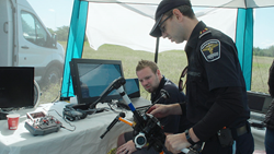 System engineer Joe Lee, and Renfrew Paramedics UAV pilot Scott Mcleod confer prior to a simulated medical rescue scenario at field trials of the Emergency Operations Airspace Management System (EOAMS), conducted near Pembrooke, Ontario.