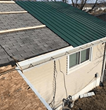 picture of a shingle roof being replaced with metal material