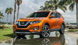 Exterior view of an orange 2018 Nissan Rogue parked on pavement surrounded by palm trees