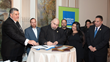 New York State Chaplain Task Force's the Rev. Marcos Miranda, center, signs documents with the Rev. Eric J. Hall, left, at HealthCare Chaplaincy Network's 2018 Wholeness of Life Gala. Photo: Ben Asen