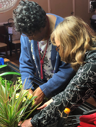 Eldergrow educator helping senior with plant