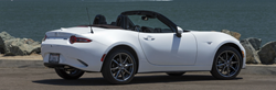 right side view of white Mazda Miata with roof down