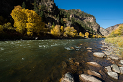 Photo shows the Colorado River flanked by fall colors east of Glenwood Springs, Colorado. Autumn