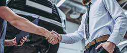 Two people shaking hands inside Nissan dealership service bay