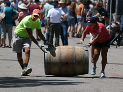 Two people rolling a wine barrel.