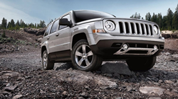 Exterior view of a silver 2014 Jeep Patriot driving on rocky terrain