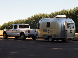 Exterior view of a 2019 Airstream Sport being pulled by a pickup truck