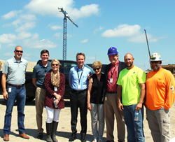 Shamrock Trading Corporation and JE Dunn representatives stand in front of tower crane