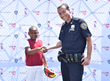 Officer Fitzgerald of the NYPD 75th precinct with helmet recipient at the JaffaCares Safety Sunday