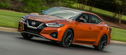 Orange 2020 Nissan Maxima driving on parkway
