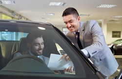 Businessman Showing Man in Vehicle a Piece of Paper