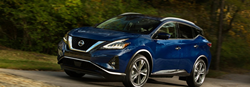 2019 Nissan Murano driving down a forested trail