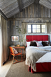 A surprising scarlet tufted headboard and bed skirt add a bold stroke of drama to patinaed wood walls in one of the guest cottage bedrooms by WRJ Design (photo by William Abranowicz).