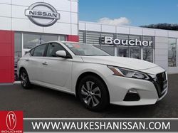 White 2020 Nissan Altima parked in front of dealership facade at Waukesha Nissan
