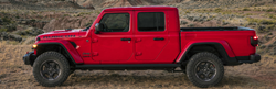 Red 2020 Jeep Gladiator from showing driver side in front of field