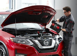 Image of a service technician installing a battery inside a Nissan vehicle