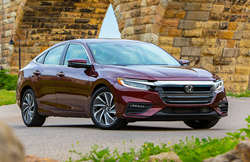 2019 Honda Insight exterior shot with dark red paint color parked beside a brick bridge