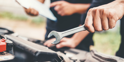 Mechanic's hand holding a wrench and repairing a car engine