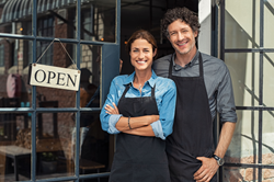 "man and woman restuarant owners smiling, standing outside restaurant doors where an ""open"" sign hangs"