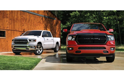 2020 Ram 1500 red and white parked near a wood building
