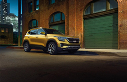2021 Kia Seltos Starbright Yellow parked by brick building dark blue sky