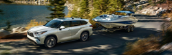 White 2020 Toyota Highlander Towing a Boat on a Lake Road
