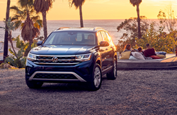 The front of a blue 2021 Volkswagen Atlas parked in a parking lot during sunset.