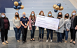 Winner holding her large check with colleagues standing on either side of her